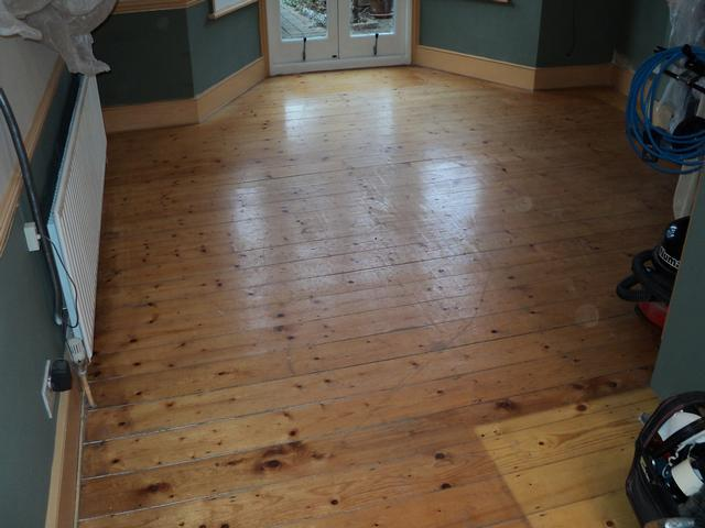 Pine flooring badly refinished with lots of scuffs and dents before renovation.