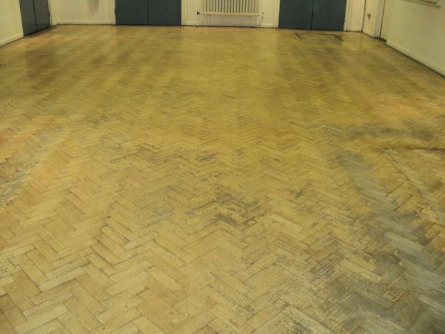 Dirty parquet school flooring before sanding with Lagler belt sander