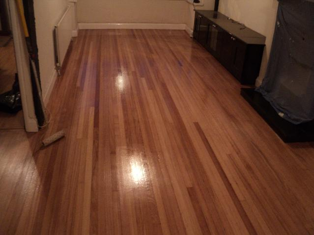 Strip flooring beautifully restored by sanding, filling and recoating tree times with clear satin lacquer