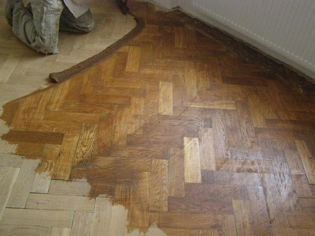 Parquet flooring gap filling with mix of resin and sand dust